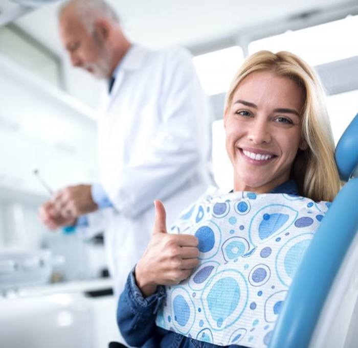 woman giving thumbs up about to get dental bridge in Indian Land